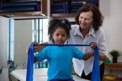 Physiotherapist assisting girl patient in performing stretching exercise from resistance band Royalty Free Stock Photography