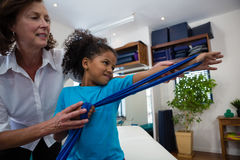 Physiotherapist assisting girl patient in performing stretching exercise from resistance band. In clinic Stock Photography