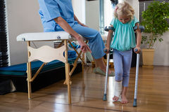 Physiotherapist assisting girl patient to walk with crutches. In clinic Royalty Free Stock Images