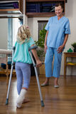 Physiotherapist assisting girl patient to walk with crutches. In clinic Stock Photos
