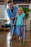 Physiotherapist assisting girl patient to walk with crutches. In clinic Stock Photo