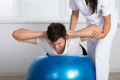 Physiotherapist Assisting Man While Doing Exercise royalty free stock image