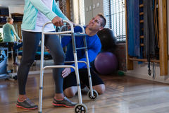 Physiotherapist assisting patient to walk with walking frame. In clinic Stock Photos