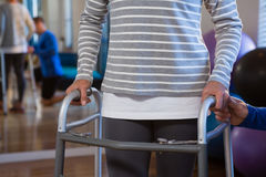 Physiotherapist assisting patient to walk with walking frame. In clinic Stock Image