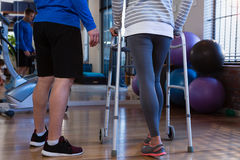 Physiotherapist assisting patient to walk with walking frame. In clinic Stock Images