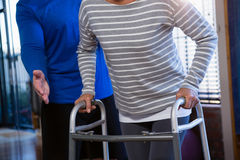 Physiotherapist assisting patient to walk with walking frame. In clinic Stock Photography