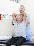 Physiotherapist Assisting Senior Man In Exercising At Rehab Cent Royalty Free Stock Image