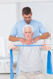 Physiotherapist assisting senior man in exercising with resistance band Royalty Free Stock Photos