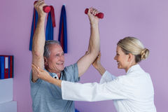 Physiotherapist assisting senior man to lift dumbbell Royalty Free Stock Photography