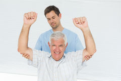 Physiotherapist assisting senior man to raise hands Royalty Free Stock Photography