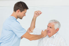 Physiotherapist assisting senior man to stretch his hand Royalty Free Stock Photo