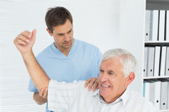 Physiotherapist assisting senior man to stretch his hand Royalty Free Stock Photos