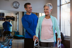 Physiotherapist assisting senior patient to walk with walking frame. In clinic Royalty Free Stock Photo