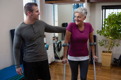 Physiotherapist assisting senior woman patient to walk with crutches. Physiotherapist assisting senior women patient to walk with crutches in clinic Royalty Free Stock Images