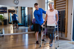 Physiotherapist assisting senior woman patient to walk with walking frame. Physiotherapist assisting senior women patient to walk with walking frame in clinic Stock Image