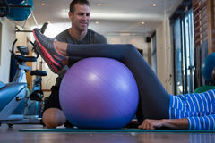 Physiotherapist assisting senior woman in performing exercise on fitness ball Stock Images