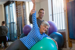Physiotherapist assisting senior woman in performing exercise on fitness ball Royalty Free Stock Photos