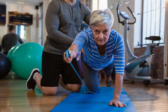 Physiotherapist assisting senior woman in performing exercise with resistance band Royalty Free Stock Photo