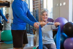 Physiotherapist assisting senior woman in performing stretching exercise with resistance band. Physiotherapist assisting senior women in performing stretching Stock Image