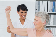 Physiotherapist assisting senior woman to stretch her hand Royalty Free Stock Photography