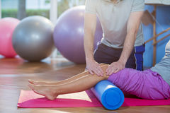 Physiotherapist assisting woman while exercising on exercise mat stock images