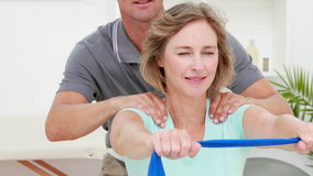 Physiotherapist checking patient stretching resistance band