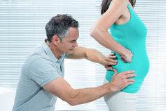 Physiotherapist checking pregnant womans lower back Royalty Free Stock Photography