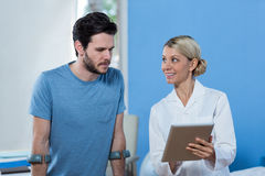 Physiotherapist discussing with patient over digital tablet. In clinic Royalty Free Stock Image