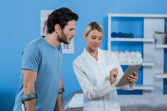 Physiotherapist discussing with patient over digital tablet. In clinic Royalty Free Stock Photography
