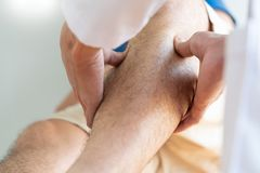 Physiotherapist doctor rehabilitation consulting physiotherapy giving exercising leg treatment with patient in physio clinic or ho. Spital royalty free stock photography