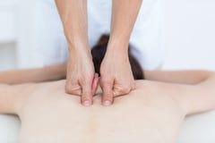 Physiotherapist doing back massage Stock Image
