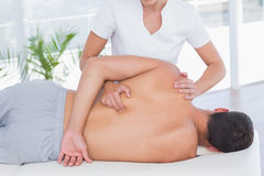 Physiotherapist doing back massage to her patient Stock Images