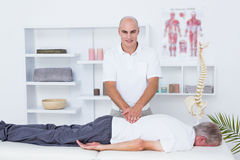 Physiotherapist doing back massage to his patient Stock Image