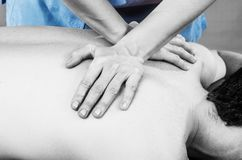 Physiotherapist doing a back massage to man patient in silhouette studio. Osteopathy. stock photography