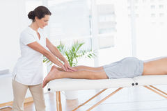 Physiotherapist doing calf massage to her patient Stock Photography
