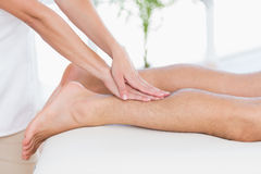 Physiotherapist doing calf massage to her patient Royalty Free Stock Image