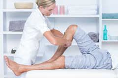Physiotherapist doing calf massage to her patient Royalty Free Stock Photography