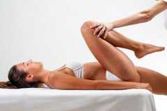 Physiotherapist doing healing massage on female legs. Stock Photos