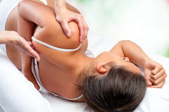 Physiotherapist doing healing treatment on female shoulder blade. Close up top view of osteopath doing healing treatment on female shoulder blade Royalty Free Stock Photo
