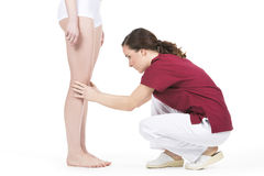 Physiotherapist doing a knee evaluation at a wpman Royalty Free Stock Image