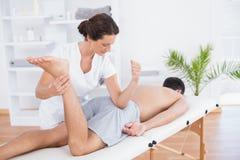Physiotherapist doing leg massage Stock Images