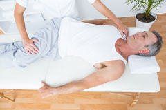Physiotherapist doing leg massage to her patient Stock Photography