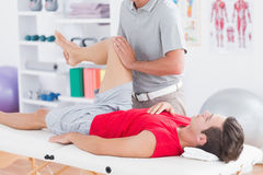 Physiotherapist doing leg massage to his patient Stock Images