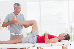 Physiotherapist doing leg massage to his patient Stock Photo