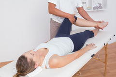 Physiotherapist doing leg massage to his patient Royalty Free Stock Images