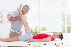 Physiotherapist doing leg stretching to his patient Stock Photos