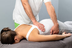 Physiotherapist doing massage on female lower back. Royalty Free Stock Photography