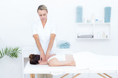 Physiotherapist doing neck massage Stock Photos