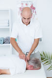Physiotherapist doing neck massage to his patient Royalty Free Stock Photo