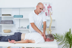 Physiotherapist doing neck massage to his patient Royalty Free Stock Image